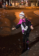 Goshen, New York - Molly McNulty of Catonsville, Maryland, reaches for bubbles on South Church Street during the Illuminate Goshen New Year's Eve Ball Drop on Dec. 31, 2016. McNulty and her family were visiting Goshen on their way home after a ski trip to the Adirondacks.