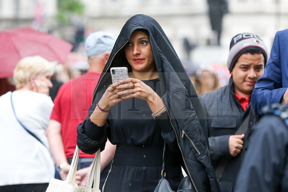 © Licensed to London News Pictures. 18/06/2019. London, UK. A woman with a mobile phone shelters from the rain under her jacket in Westminster. The Met Office has issued a yellow weather warning for London as torrential rain, hail and lightning is forecasted. Photo credit: Dinendra Haria/LNP