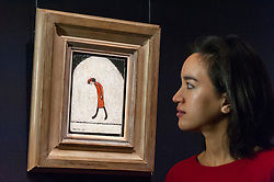 """© Licensed to London News Pictures. 18/11/2016. London, UK. A staff member views """"Woman in Red"""" by Laurence Stephen Lowry (est. GBP60-80k), at the preview at Sotheby's of works on view at four upcoming November auctions featuring Modern & Post-War British Art, A Painter's Paradise (Julian Trevelyan & Mary Fedden at Durham Wharf), Scottish Art and Picasso Ceramics from the Lord & Lady Attenborough Private Collection. Photo credit : Stephen Chung/LNP"""