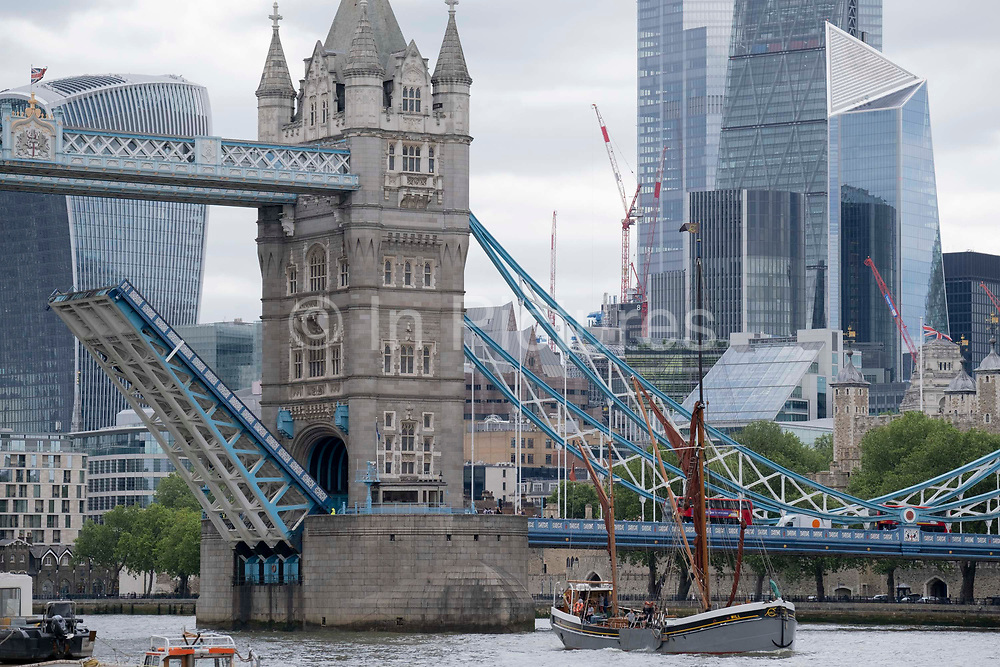 A tall-masted Thames barge passes beneath Tower Bridge that has raised its bascules, on the river Thames, on 11th June 2021, in London, England.