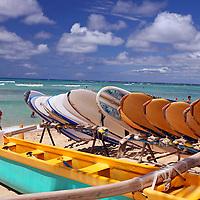 Surfboards and outrigger canoes await rental on Waikiki Beach in Honolulu, Oahu, Hawaii.