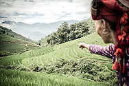 Red Dao woman of Thanh Kim Commune points to a paddy field with her finger, Sapa District, Lao Cai Province, Vietnam, Southeast Asia