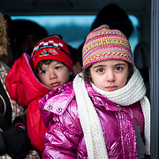At a refugee assistance point, two miles across the Macedonian-Serbian border, a Syrian family waits to be transported to Presevo, where they will catch the train or bus to the Croatian border, on their way to Western Europe. The children wear new, warm clothes donated by NGOs. Near Miratovac, Serbia, January 2016.