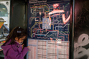A young girl with a bus route map of London with reflections of the Primark screen ads in Oxford Street.