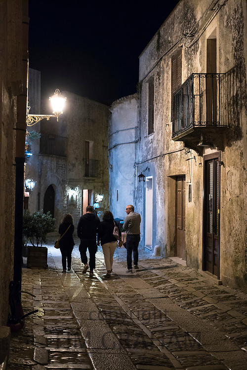 Tourists strolling on stone cobbles at night in cobbled street alleyway in Erice, Sicily, Italy