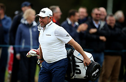 Lee Westwood carrying his own clubs after his caddie goes for hot drinks during day two of the British Masters at Walton Heath Golf Club, Surrey.
