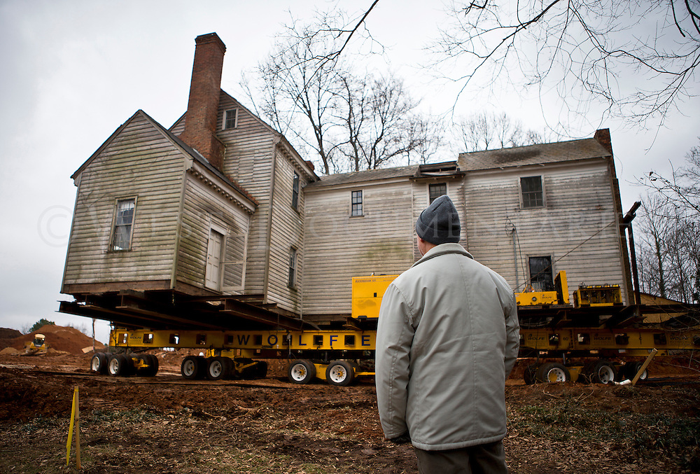 Mike Schmidt, of Raleigh, who lives in the Crabtree Heights neighborhood where the Crabtree Jones House resides, watches the massive mechanical trailer move the 219-year-old house 460 feet to its new location within the same neighborhood on Feb. 4. The Crabtree Jones House, built in 1795 on what's now Wake Forest Road, will be moved to make way for an apartment complex.