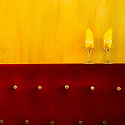 Two water glasses stuffed with yellow napkins against a beautiful yellow wall at the Van Gogh Cafe in Arles, France.