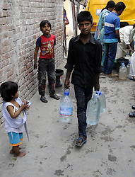 A Pakistani boy carries water bottles after filling drinking water at a distribution point on the UN World Water Day in eastern Pakistan s Lahore, March 22, 2013. According to the World Bank, about 70 percent of Pakistan's population does not have the access to safe potable water., March 22, 2013. Photo by Imago / i-Images...UK ONLY.