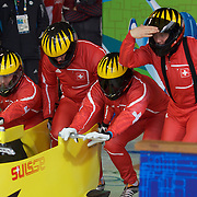 """Winter Olympics, Vancouver, 2010.The Switzerland team prepare themselves in the start area during the Bobsleigh Four-man competition  at The Whistler Sliding Centre, Whistler, during the Vancouver Winter Olympics. 26th February 2010. Photo Tim Clayton..'BOB'..Images from the Four-man Bobsleigh Competition. Winter Olympics, Vancouver 2010..History was made at the Whistler Sliding Centre when the USA four-man bobsleigh team, led by Steven Holcomb took the Gold. The first time since 1948, a gap of 62 years, since the USA have won an Olympic Bobsleigh gold and they did it with their sleigh named """"Night Train""""...The four days of practice and competition show the tension, nervousness and preparation as the teams of hardened men cope with the challenge of traveling at average speeds of over 150 km an hour. Indeed, five teams had already pulled out of the event before the opening heats because of track complexity, speed and fear, and on the final day, another four teams did not start after six crashes in the first two heats...Teams warm up behind the start complex, warming muscles in the cold in preparation for the explosive start. Many teams prepare in silence, mentally preparing themselves as they wait at the top of the run, in the bobsleigh sheds and the loading areas for their turn. When it's time to slide each team performs it's own starting ritual, followed by the much practiced start out of the blocks for just over four seconds, the teams are then in the hands of the accomplished drivers as they hurtle down the track for just over fifty seconds...Spectators clamber for the best position on track to see the sleighs for a split second, many unsuccessfully try to capture the moments on camera, The rumble of the sleigh is heard then the crowds gasp as it hurtles past in a blur...The American foursome of  Steven Holcomb, Justin Olsen, Steve Mesler and Curtis Tomasevicz finished with a pooled four-heat time of 3min 24.46sec. The German team led by Andre Lange won the Silve"""