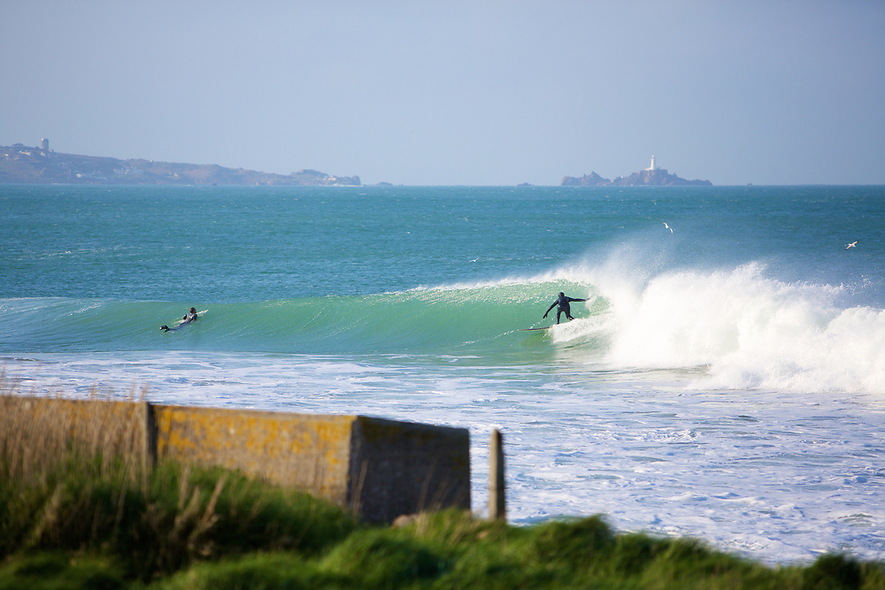 People surfing the waves at St Ouen's Bay, Jersey with the view of Corbiere lighthouse in the distance