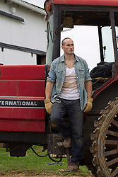 farm worker standing on a tractor