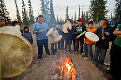 "First Nation Dene youth beat drums near a fire during a spiritual gethering in Reliance after a group returns on a canoe trip from the Upper Thelon River is ""the place where God began.""  Sparsely populated, today few make it into the Thelon. Distances are simply too far, modern vehicles too expensive and unreliable. For the Dene youth, faced with the pressures of a western world, the ties that bind the people and their way of life to the land are even more tenuous. Every impending mine, road, and dam construction threatens to sever these connections. In July and August, 2011 a group of youth paddled to their ancestral hunting ground and spiritual abode.  this next generation of young leaders will be the ones who will need to speak for the Thelon the loudest. (Photo by Ami Vitale)"