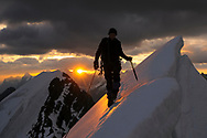 Impressionen von der Hochtour mit Aufstieg auf das Morgenhorn und Überschreitung und Abstieg via Weisse Frau an einem bewölkten Sommertag. Alpinist kurz vor dem Gipfel der Weissen Frau beim Sonnenaufgang.