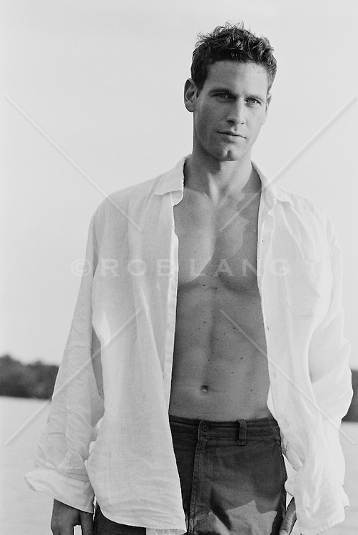 Man in an open white shirt looking at camera