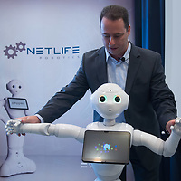 Man interacts with a Pepper customer service robot that takes part in a press conference introducing the development plans of Hungary's Netlife Robotics company in Budapest, Hungary on Sept. 6, 2018. ATTILA VOLGYI