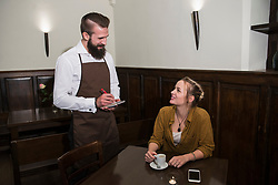 Manager taking order from beautiful woman at restaurant