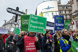 London, UK. 1st December, 2018. Environmental campaigners pass through Piccadilly Circus on the Together for Climate Justice demonstration in protest against Government policies in relation to climate change, including Heathrow expansion and fracking. Following a rally outside the Polish embassy, chosen to highlight the UN's Katowice Climate Change Conference which begins tomorrow, protesters marched to Downing Street.