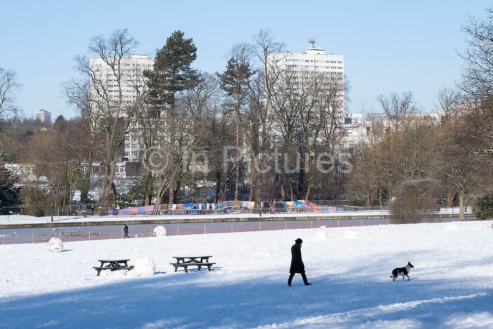 Small figures of people are part of a winter scene in the snow in Canon Hill Park in Moor Green with the backdrop of blocks of high rise flats on 25th January 2021 in Birmingham, United Kingdom. Deep snow arrived in the Midlands giving some light relief and fun during the current lockdown for people who simply enjoyed the weather.