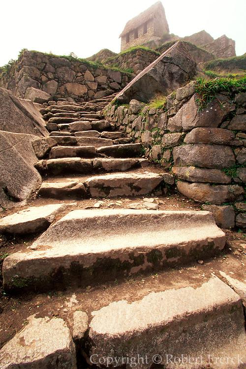 PERU, HIGHLANDS, PREHISPANIC, INCA Machu Picchu; Inca trail through terraced fields below the Hut of the Caretaker, above the city