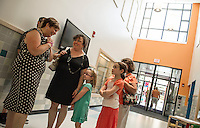 Mill Brook Elementary School Principal Cheryl Halley welcomes Michelle Langille and her daughters Ellie (incoming kindergarten student) and Katie with Carol Wheeler as they arrive for a tour on Sunday afternoon during the grand opening.    (Karen Bobotas/for the Concord Monitor)
