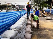 "30 DECEMBER 2013 - BANGKOK, THAILAND: Anti-government protestors put sandbags across Ratchadamnoen Road in Bangkok. Violence around the anti-government protest sites has escalated in recent days and several protestors have been hurt by small explosive devices thrown at their guard posts. As a result, protestors are fortifying their positions with sandbags and bunkers. Suthep Thaugsuban, the leader of the anti-government protests in Bangkok, has called for a new series of massive protests after the 1st of the year and said it the shutdown, or what he described was the seizure of the capital, would be the day when ""People's Revolution"" would ""begin to end and uproot the Thaksin regime.""          PHOTO BY JACK KURTZ"