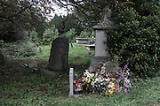 A desaturated cemetery landscape of flowers laid at a contemporary gravestones and in the distance, Victorian memorials.