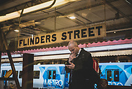 Melbourne, Australia - August 22, 2017: A man looks at his phone while standing on the station platform at Flinders Street Station, the central transportation hub in Melbourne, Australia.