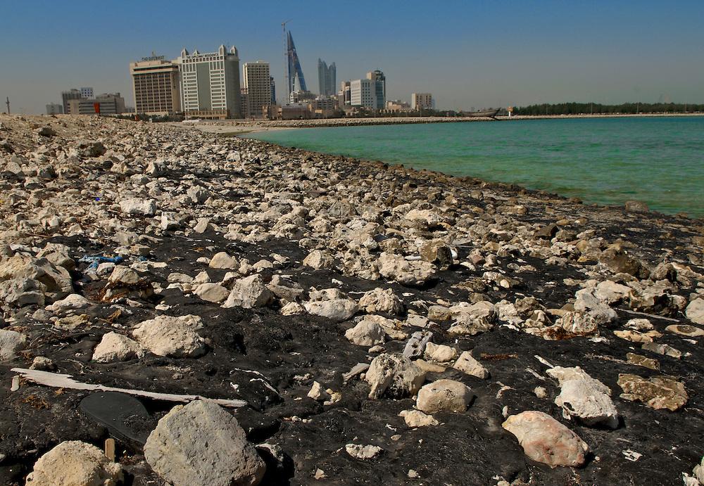 Bahrain, ölverschmutzter Strand in Manama City. Skyline am Horizont.   Bahrain, Oil polluted beach in Manama City. Skyline on the horizon.