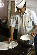 Pratap Singh cooking in the kitchen of the Indian Coffee House, Baba Kharak Singh Marg, New Delhi, India.The Coffee House dates back almost fifty years, first in central Connaught Place, then Janpath and now at the top of a rather shabby shopping centre. Still run by the Indian Coffee Workers Cooperative Society, it was a regular haunt for politicos in Delhi and It's clientele is still well read and intellectual. new Delhi, India