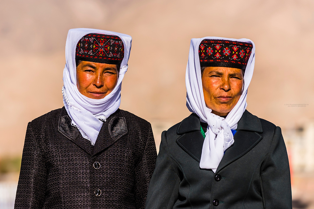 Tajik women, Tashkurgan (means Stone Fortress in Uyghur), at 10,100 feet, along the Karakoram Highway. It was a caravan stop on the Silk Road and all routes of the Silk Road converged here to journey southward to Pakistan. It sits on the borders of both Afghanistan and Tajikistan, and is close to the border of Kyrgyzstan and Pakistan.  The majority population in the town are ethnic Mountain Tajiks. Xinjiang Province, China.