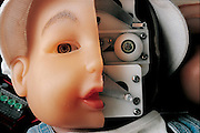 Baby It's skin partially removed to reveal its inner workings, this prototype robot baby can mimic the facial expressions of a human infant by changing the contours of its lifelike rubber face. Called BIT, for Baby IT, the mechanical tot is yet more proof that much robotic research will see its first commercial application in the toy and entertainment industry. My Real Baby, the market version of BIT, is scheduled to debut in US stores in late 2000; it is a collaboration between Hasbro, the US toy giant, and iRobot, a small company started by MIT researcher Rodney Brooks.  Somerville, MA. From the book Robo sapiens: Evolution of a New Species, page 229.
