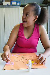 Teenage girl with learning disability making a picture of a flower in an art class,