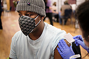 27 MARCH 2021 - DES MOINES, IOWA: JUSTIN PINKNEY gets a COVID-19 vaccination from a nursing student during a COVID-19 (Coronavirus) vaccination clinic at Corinthian Baptist Church in Des Moines, Saturday. The clinic was organized by Broadlawns Medical Center and the United Way and provided more than 1,100 shots to Des Moines area residents. The clinic was a part of an effort to reach communities of color in Iowa, who are vaccinated at rates below the state average.      PHOTO BY JACK KURTZ