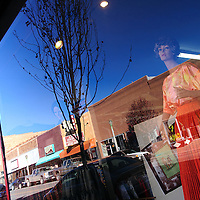 111912  Adron Gardner<br /> <br /> Coal Avenue is reflected in the glass of the Gallup Fabric Shop store front in Gallup Tuesday.