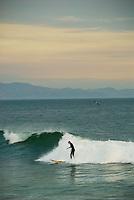 A woman rides the surf at Leadbetter Beach, Santa Barbara, California.