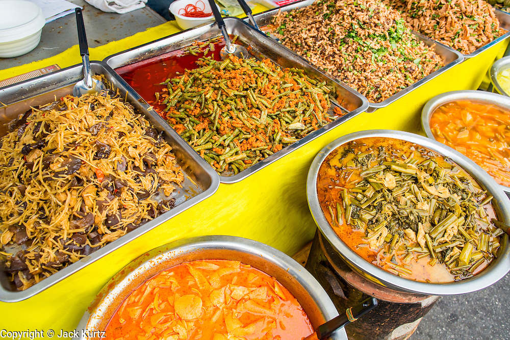 17 OCTOBER 2012 - BANGKOK, THAILAND:   Thai curries and stir fries, all made with tofu instead of meat, at the Vegetarian Festival food fair on Yaowarat Road in Chinatown in Bangkok. The Vegetarian Festival is celebrated throughout Thailand. It is the Thai version of the The Nine Emperor Gods Festival, a nine-day Taoist celebration celebrated in the 9th lunar month of the Chinese calendar. For nine days, those who are participating in the festival dress all in white and abstain from eating meat, poultry, seafood, and dairy products. Vendors and proprietors of restaurants indicate that vegetarian food is for sale at their establishments by putting a yellow flag out with Thai characters for meatless written on it in red.      PHOTO BY JACK KURTZ