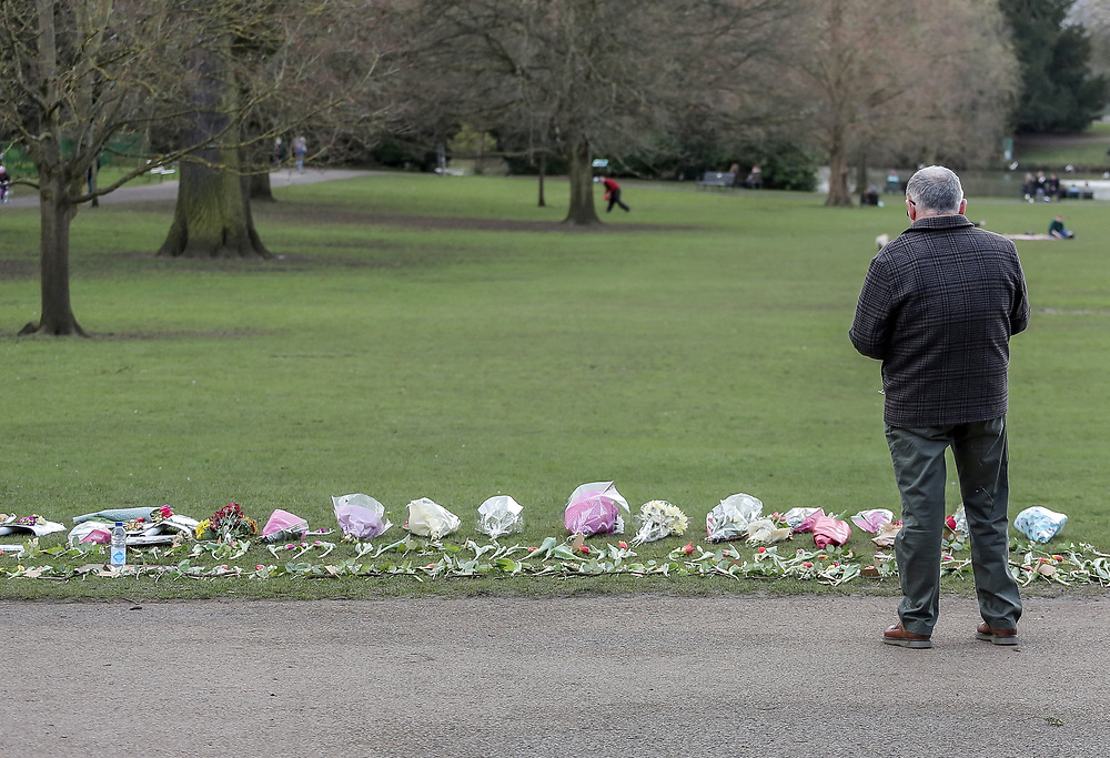 13th, March, 2021. Cheltenham, England. A member of the public looks at the array of flowers laid out in memory of Sarah Everard.