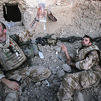 6th July 2007. Kajaki, Helmand Province Afghanistan. Lance Corporal Andrew Howe of 1 Royal Anglian C Coy is given fluids intravenously by a combat medic as treatment for heat exhaustion in a ruined compound during a firefight with Taliban fighters in Kajaki, Helmand Province, Afghanistan on the 6th July 2007.