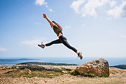 A young woman in her twenties leaping across rocks, full of joy on a sunny day, at the summit of Cadillac Mountain of Acadia National Park, Maine