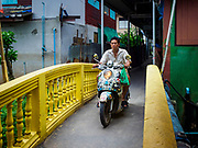 02 AUGUST 2018 - PAK KRET, NONTHABURI, THAILAND: A motorcycle crosses a bridge over a small stream on Ko Kret. Ko Kret (also spelled Koh Kret) is a small island in the Chao Phraya River in Nonthaburi province north of Bangkok. It is about 2 km long and 1 km wide. It has seven main villages, the largest and most populous being Ban Mon. Ko Kret was created in 1722 when a canal was dug in the Chao Phraya River to bypass a bend. Most of the people on the island are ethnically Mon, from the hills of western Thailand and eastern Myanmar (Burma). The island is popular as a weekend daytrip from Bangkok. The island is famous for the Mon style pottery made on the island.      PHOTO BY JACK KURTZ