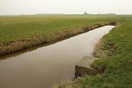 Buitendijks kweldergebied van waterschap Blija Buitendijks.<br /> Waterschap Blija Buitendijks is het kleinste waterschap van Nederland. Het waterschap beheert 100 hectare weiland, gelegen bij het dorp Blija in het noorden van Friesland, tussen de Waddenzeedijk en zomerdijk. Direct achter de 2,25 m +NAP hoge zomerdijk bevindt zich het uitgestrekte kweldergebied van de Waddenzee. Bij hoogwater (vloed) stroomt het buiten de zomerdijk gelegen kwelder regelmatig onder water. Bij extreem hoog water, bijvoorbeeld bij springtij en noordwesterstorm komt het zeewater vanuit de Waddenzee ook over de zomerdijk. De door het waterschap beheerde polder komt dan geheel onder water te staan, soms zelfs tot halverwege de Waddenzeedijk. Bij afgaand tij (eb) stroomt het zeewater via de klepstuwen in de zomerdijk terug naar de Waddenzee. De afgebeelde watergang (afwateringssloot) bevindt zich langs de zomerdijk met daarin de betonnen duiker met klepstuw. Op de achtergrond (in de verte) is de Waddenzeedijk (op Deltahoogte) te zien.
