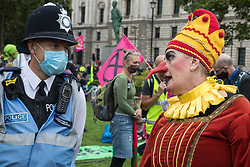 A Metropolitan Police liaison officer speaks to a jester from Extinction Rebellion at a 'Carnival of Corruption' protest against the government's facilitation and funding of the fossil fuel industry on 3 September 2020 in London, United Kingdom. Extinction Rebellion activists are attending a series of September Rebellion protests around the UK to call on politicians to back the Climate and Ecological Emergency Bill (CEE Bill) which requires, among other measures, a serious plan to deal with the UK's share of emissions and to halt critical rises in global temperatures and for ordinary people to be involved in future environmental planning by means of a Citizens' Assembly.