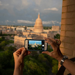 A woman takes a cellphone picture as a bank of mammatus clouds follows a rainstorm over the Texas Capitol dome in Austin while a spring weather system blows through central Texas. The mammatocumulus are characterized by cotton-like puffiness and dramatic formations.