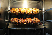 Whole grilled chicken on a skewer