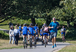 Licensed to London News Pictures. 21/09/2021. Surrey, UK. Walkers, cyclists and runners enjoy the sunshine in Richmond Park, south-west London today as weather forecasters predict warm autumnal weather for the next 7 days with highs of 24c.  Photo credit: Alex Lentati/LNP