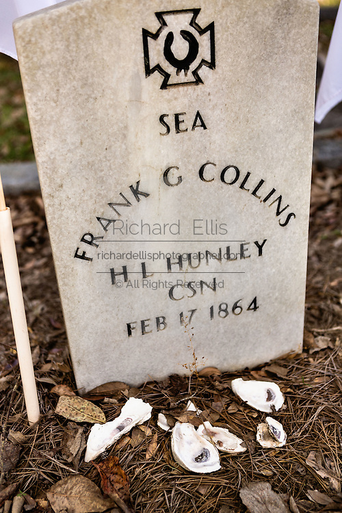 Grave site of the civil war era submarine HL Hunley sailors in historic Magnolia Cemetery in Charleston, South Carolina. The shells and coins at the tomb are a mark of respect from visitors.