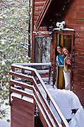 Three women smiling from cabin door in winter, San Bernardino National Forest, California USA