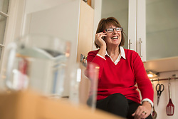 Senior woman sitting in the kitchen and talking on a smartphone, Munich, Bavaria, Germany