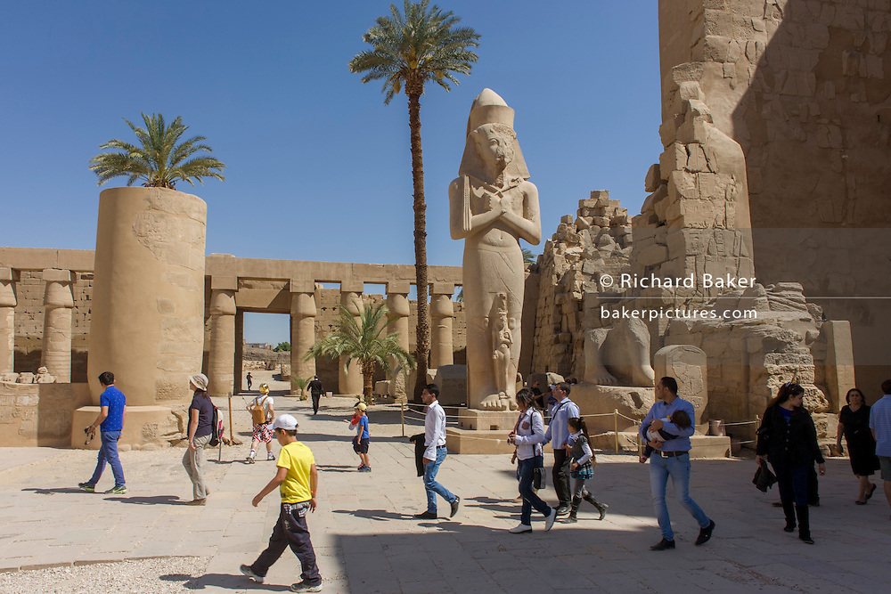 Tourists walk past the giant colossus of Pharaoh Ramesses ll and Bintanat at the ancient Egyptian Temple of Karnak, Luxor, Nile Valley, Egypt.